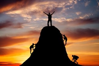 Man on top of the mountain and the other people to climb up